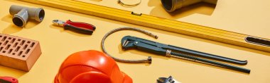panoramic shot of spirit level, calipers, plumbing hose, pipe connector, brick, pliers and monkey wrench on yellow background
