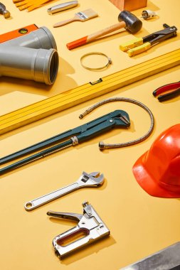 high angle view of industrial tools, plumbing hose, helmet and brush on yellow background