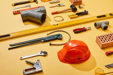 high angle view of industrial tools, helmet, bricks, measuring tape, brush, and plumbing hose on yellow background