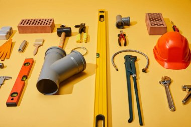 high angle view of industrial tools, bricks and helmet on yellow background