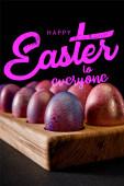 Selektive Fokussierung von Ostereiern auf Holzbrettern auf schwarz mit frohen Ostern für alle Abbildung