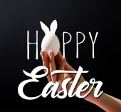 Cropped view of woman holding chicken egg isolated on black with happy Easter illustration