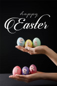 Selective focus of Easter eggs on wooden board on black with happy Easter illustration