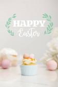 Selektivní zaměření cupcake s velikonočními vejci na šedém pozadí s veselou velikonoční ilustrací
