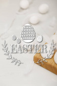 Selective focus of eggs on wooden egg tray and feathers on white background with Easter illustration