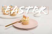 Selektivní zaměření cupcakes na talíř s vidličkou a kulaté desky s cukrovou miskou na šedém pozadí s velikonoční ilustrací