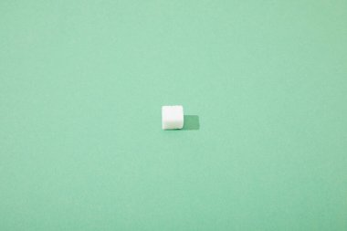 lump sugar cube on green background with copy space