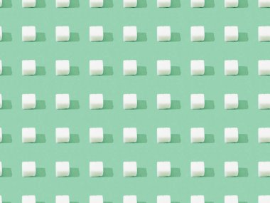 top view of lump sugar on green, seamless background pattern