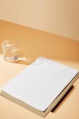 list papíru a tužky u sklenice vody na béžovém povrchu