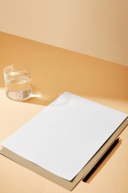 Sheet of paper and pencil near glass of water on beige surface stock vector