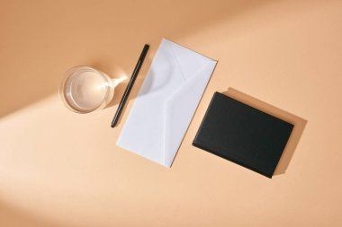 Top view of envelope, pen, glass of water and black notebook on beige background stock vector