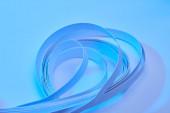 zblízka pohled na zakřivené barevné papírové pruhy na neonově modrém pozadí