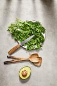 Horní pohled na zeleň na talíři, noži, stěrkách a avokádových půlkách na šedém pozadí
