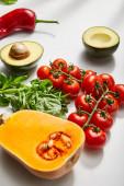 Dýně, cherry rajčata, bazalka, chilli paprika a avokádo půlky na bílém pozadí