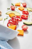 Válogatott fókusz tál és vágott zöldségek avokádó szeletek fehér alapon