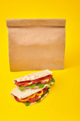 fresh sandwiches with salami, pita, vegetables and cheese on yellow background near paper takeaway bag