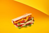 frisches Sandwich mit Salami, Pita, Gemüse und Käse auf gelbem Hintergrund