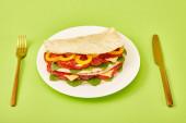 čerstvý sendvič se salámem, pitou, zeleninou a sýrem podávaný na talíři u zlaté vidličky a nůž na zeleném pozadí