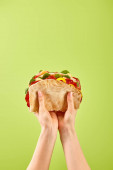 Fotografie partial view of woman holding fresh sandwich with salami, pita, vegetables and cheese isolated on green
