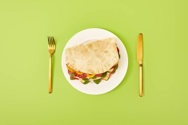 Top view of fresh sandwich with salami, pita, vegetables and cheese served on plate near golden fork and knife on green background stock vector