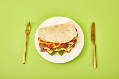 Fresh sandwich with salami, pita, vegetables and cheese served on plate near golden fork and knife on green background stock vector