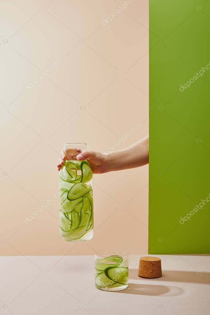 Cropped view of female hand holding bottle filled with water and sliced cucumbers on beige and green background stock vector