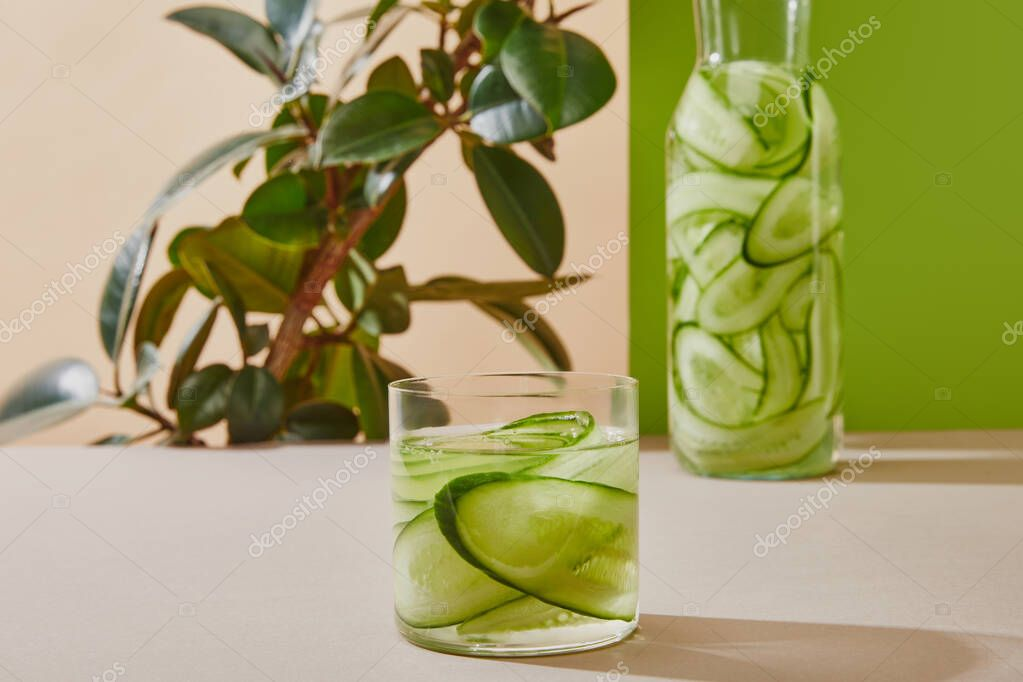 Selective focus of glass and bottle filled with water and sliced cucumbers and plant on beige and green background stock vector