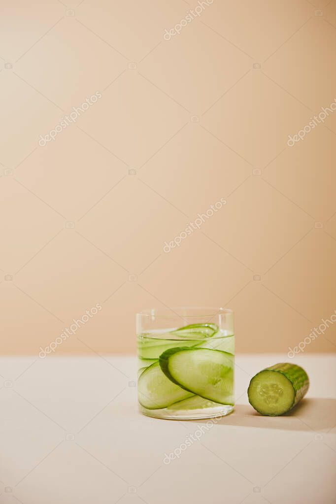 Glass of water with sliced cucumbers on table isolated on beige stock vector