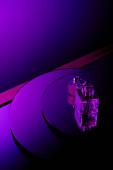 Lila parfümös palackok kerek tükrös felületen sötét lila háttérrel