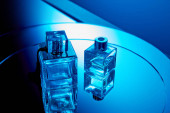 Blue perfume bottles with reflection on round mirror surface