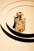 Luxusní parfém láhev na kulatém zrcadlovém povrchu s odrazem