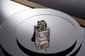 Fialová lahvička parfému na šedém kulatém zrcadlovém povrchu s odrazem