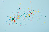 top view of colorful confetti scattered on blue background