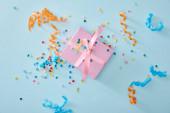 felső nézet színes konfetti közel rózsaszín ajándék doboz kék háttér