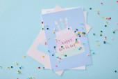 felső nézet színes konfetti közel születésnapi üdvözlőlapok kék háttér