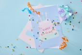 horní pohled na barevné konfety v blízkosti narozeninové přání na modrém pozadí