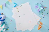 felső nézet színes konfetti közelében üres papír és ajándékdobozok kék háttér