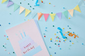 top view of colorful confetti near birthday greeting card on blue background