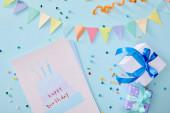 felső nézet színes konfetti közelében ajándékdobozok és születésnapi üdvözlőkártya kék háttér