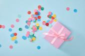 vrchní pohled na barevné konfety u růžové dárek na modrém pozadí