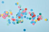 vrchní pohled na barevné kulaté konfety na modrém pozadí