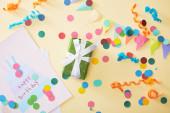 vrchní pohled na slavnostní barevné konfety a dárek s blahopřání k narozeninám na béžovém pozadí