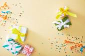 Fotografie vrchní pohled na slavnostní barevné konfety a dárky na béžovém pozadí