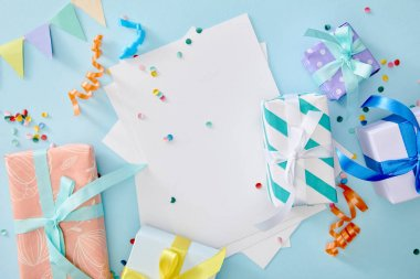 Top view of colorful confetti near blank paper and gift boxes on blue background stock vector