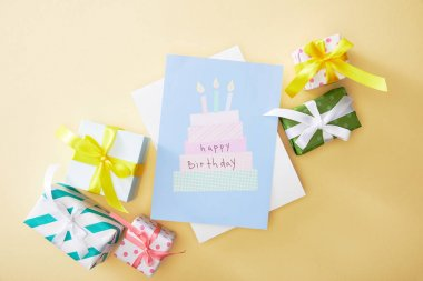 Top view of festive colorful gifts and happy birthday greeting card on beige background stock vector