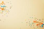 vrchní pohled na slavnostní barevné konfety na béžovém pozadí