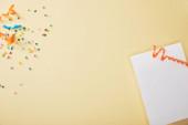 vrchní pohled na slavnostní barevné konfety v blízkosti prázdný papír na béžovém pozadí