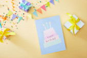 top view of festive colorful confetti and gift boxes near happy birthday greeting card on beige background