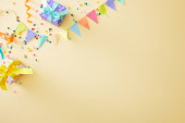 top view of festive colorful confetti and gift boxes on beige background
