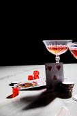 Hrací karty, kostky a žetony v blízkosti sklenic koktejlu na bílém povrchu izolované na černém